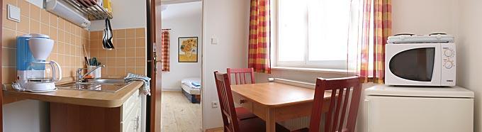 Kuchyň a jídelna třílůžkového apartmánu číslo 2. V každé kuchyni je lednice, mikrovlnka, dvouplotýnkový vařič, varná konvice, talíře a příbory.